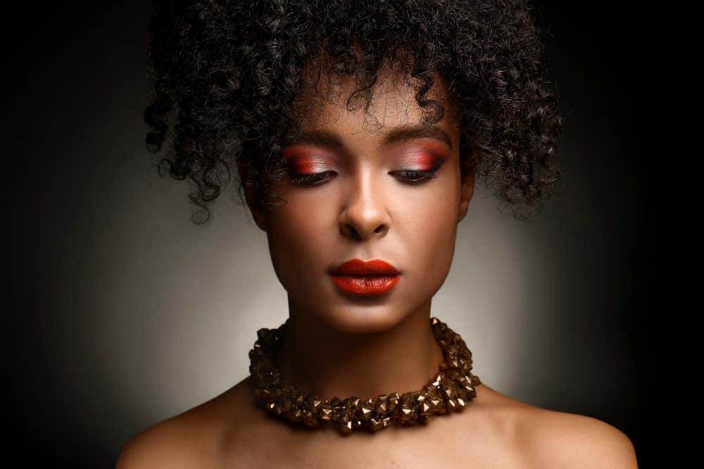 Portrait of beautiful African-American woman on dark background