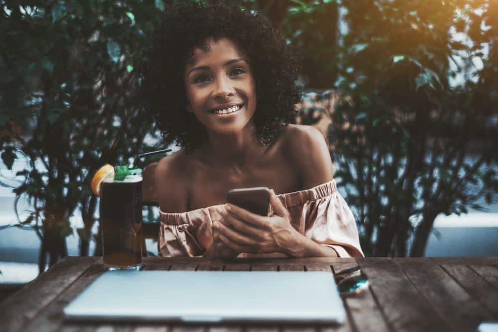 A laughing young curly haired Brazilian female with the smartphone, notebook and a cocktail in a street bar.