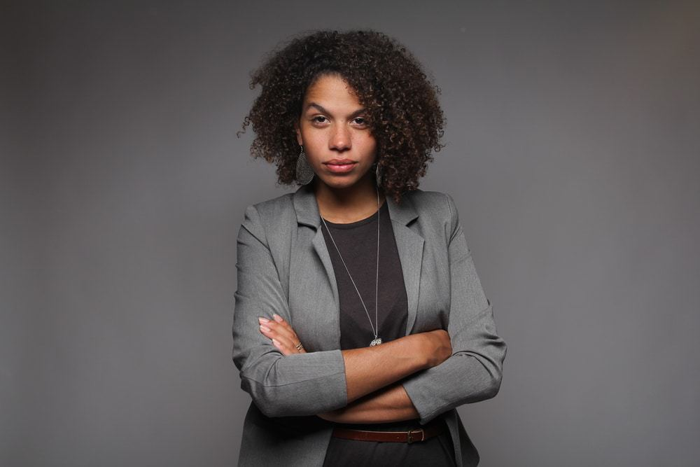 African American female with curly type 3b hair treated with safflower oil wearing a gray jacket and black shirt.