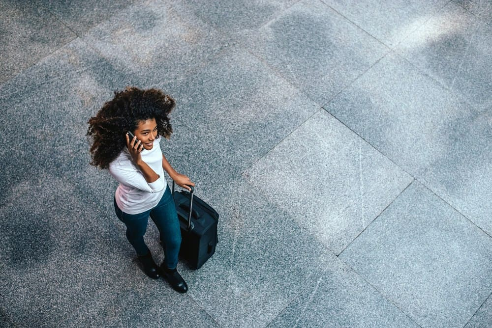 Top view of woman with type 3c curly hair carrying a trolley bag talking on phone as she prepares to board an airplane.