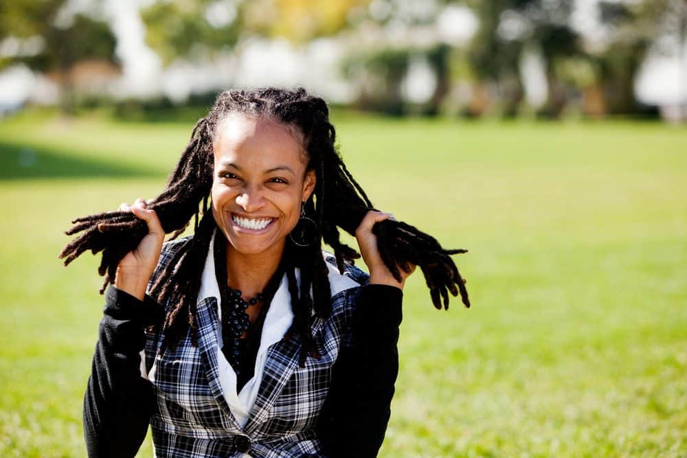 A young African American woman having fun sitting outside holding groups of locs in both hands.
