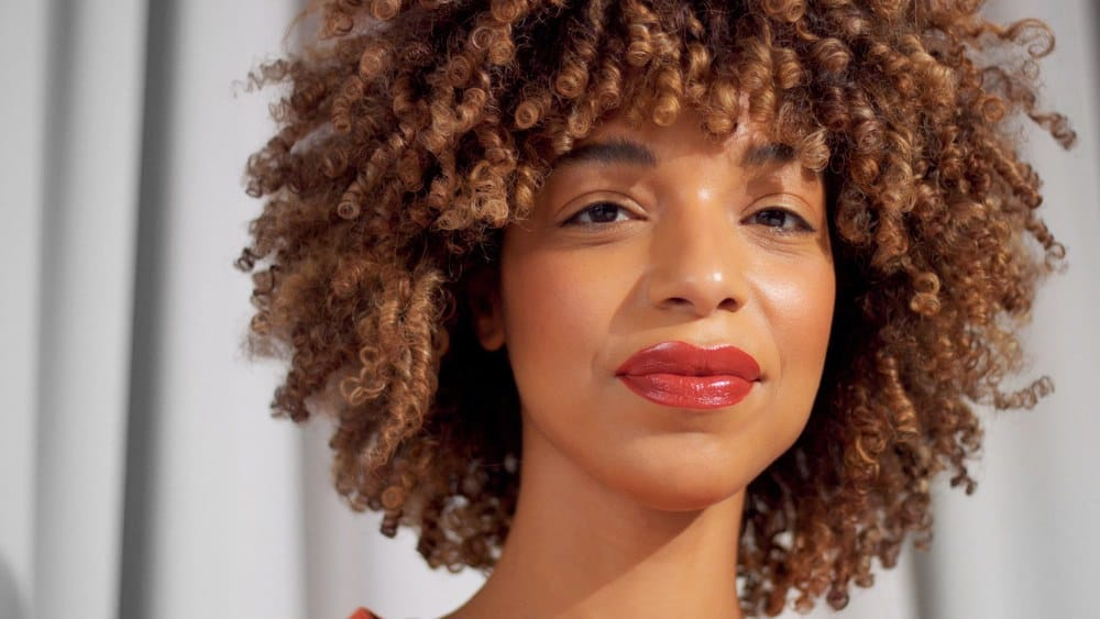Shirley Temple Curls: Learn How to Recreate the Classic Hairdo. Mixed race black woman with curly hair and natural warm make-up for dark skin watching to the camera Slightly smiling.