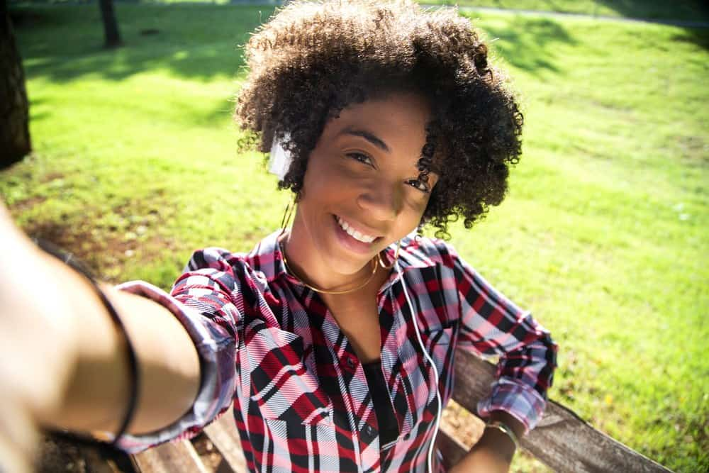 Closeup portrait of smiling young attractive African American woman holding a smartphone, taking selfie photo and standing in the park with blurred plants and grass in the background.