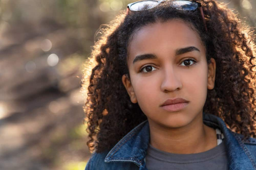 Outdoor portrait of beautiful mixed race teenager female looking thoughtful with curly hair.