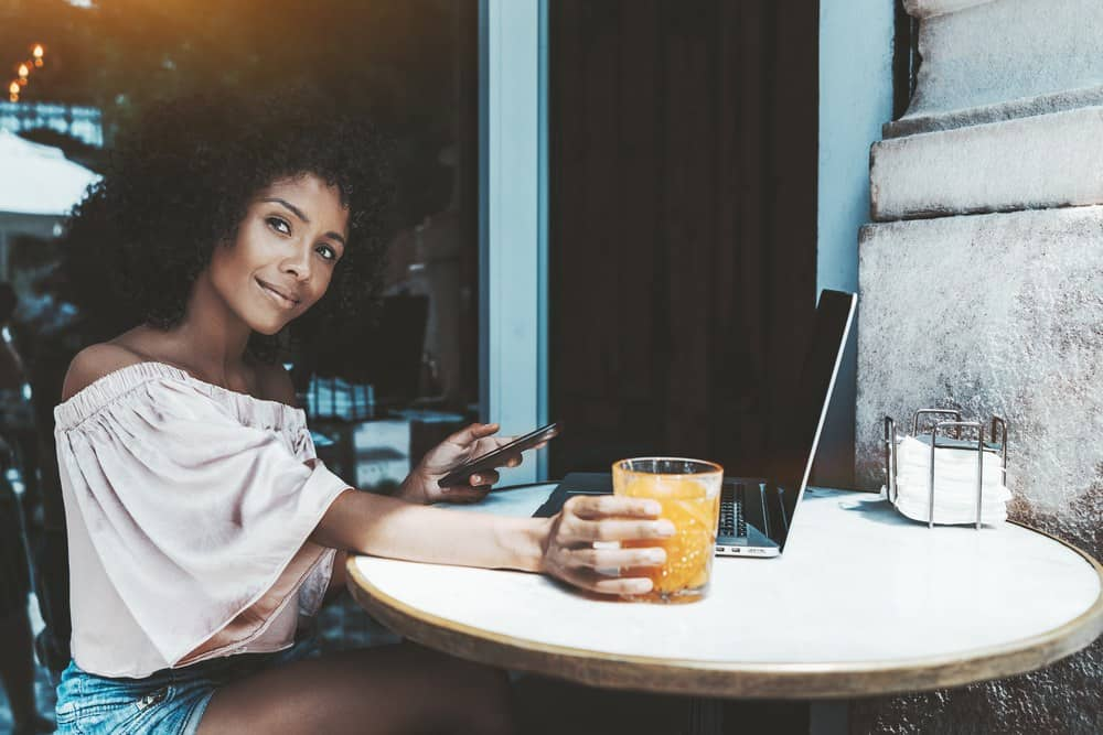 Charming young curly hair Brazilian woman in a street cafe with the cellphone, netbook, and the glass of orange juice.