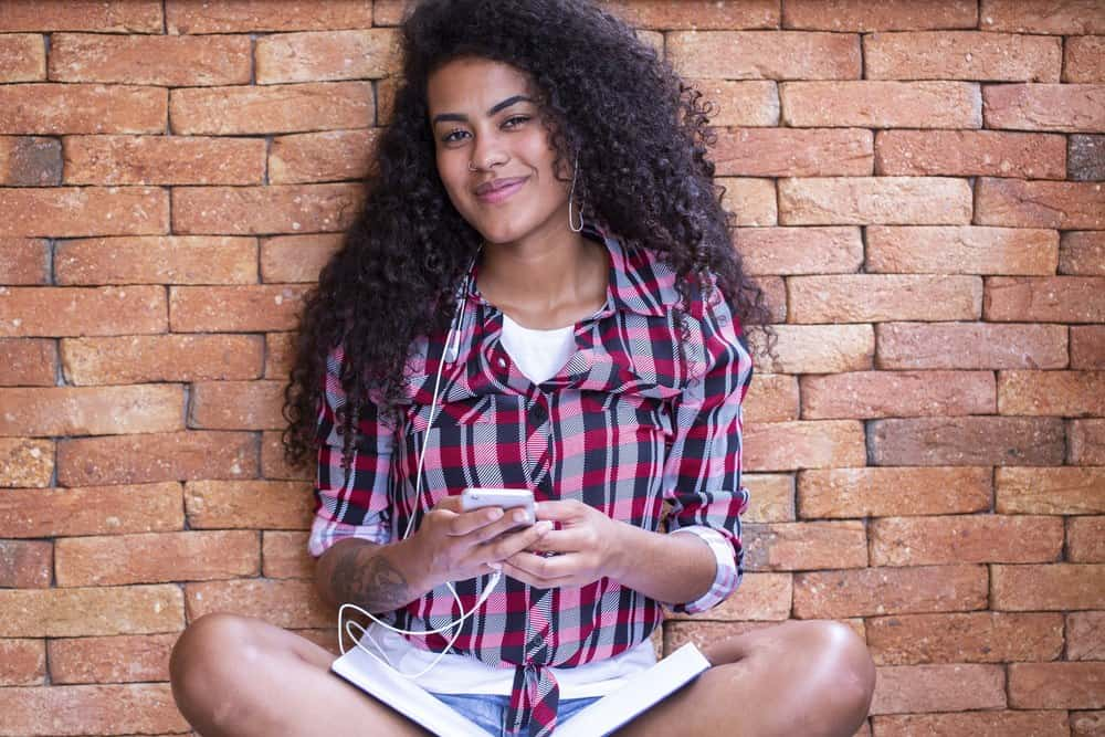 Happy Indian girl with wavy type 3b hairstyle sitting with bricked background using an Apple iphone. She's wearing a red and blue plaid shirt, blue jean shorts, and a nose ring.