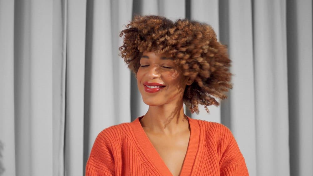 Beautiful closeup portrait of mixed race black woman smiling and shake her type 3a naturally curly hair while smiling.