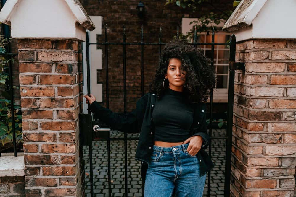 Portrait of cute African American women with naturally curly hair standing outside on a street corner holding the rails of a black iron gate.