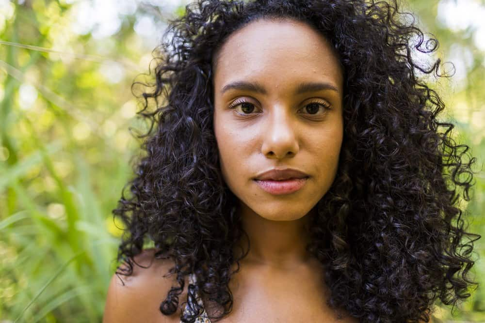 Young Afro American woman at sunset with very curly hair looking directly into the camera.