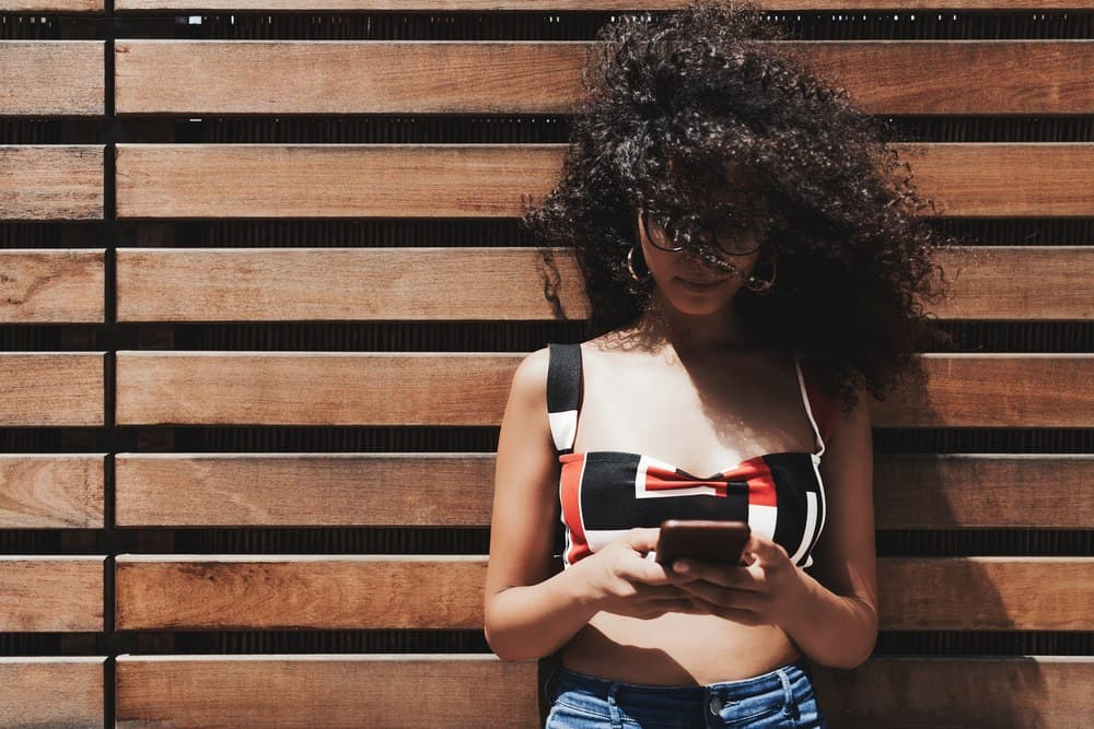 Young white woman wearing sunglasses leaning on a wooden wall using an Apple iPhone.
