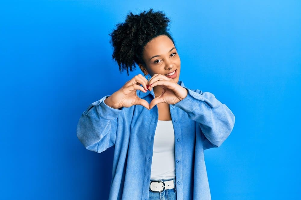 Young African American girl wearing casual clothes smiling in love doing heart symbol shape with hands.