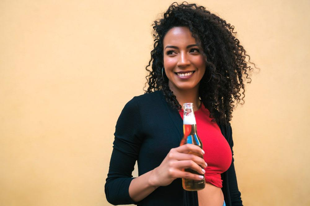 Young American Latin woman with almond oil treated curly hair enjoying and drinking a bottle of coke.
