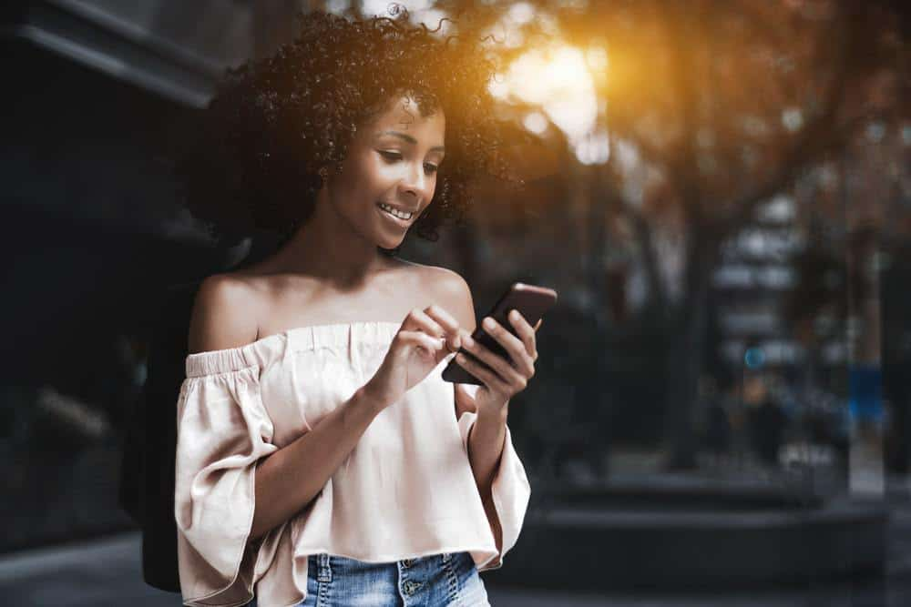 Charming cheerful African-American female with a naturally curly straw curls carrying an Android cellphone on a summer city street typing a message while standing outdoors near a glass wall.