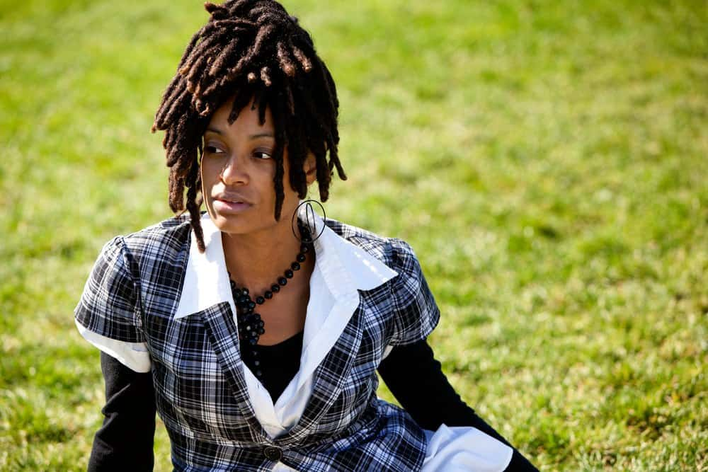 African American woman isolated on grass wearing loc extensions.