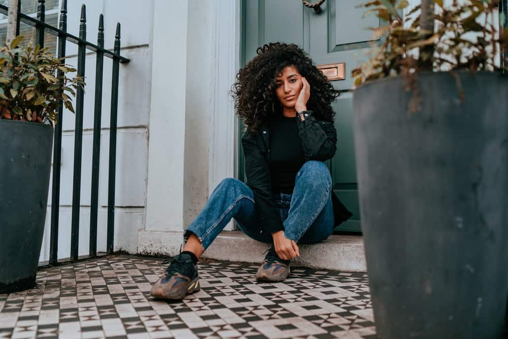Young women with curly hair pondering the benefits of using sunflower oil for hair growth in a charming photo where she's sitting outside in front of a door.