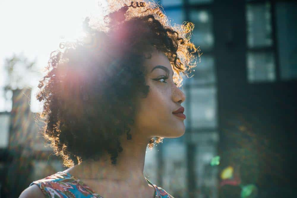 Latin woman with curly hair that been treated with cedarwood oil standing in the city looking off into the distance.