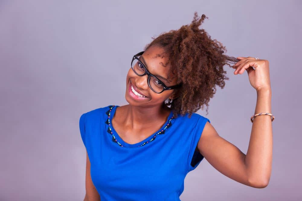 Cute black girl with 4c curly hair wearing a blue short, black reading glasses and orange and blue bracelet.