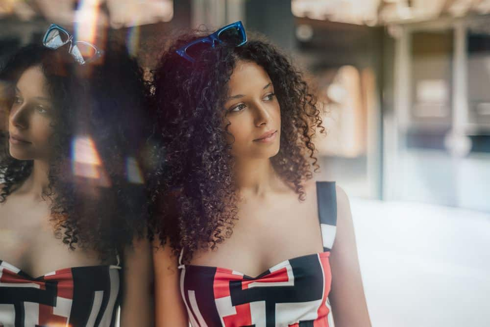 Black women wearing a black, white and red shirt with hair treated with arnica oil. She's leaning on a wall wearing blue sunglasses.