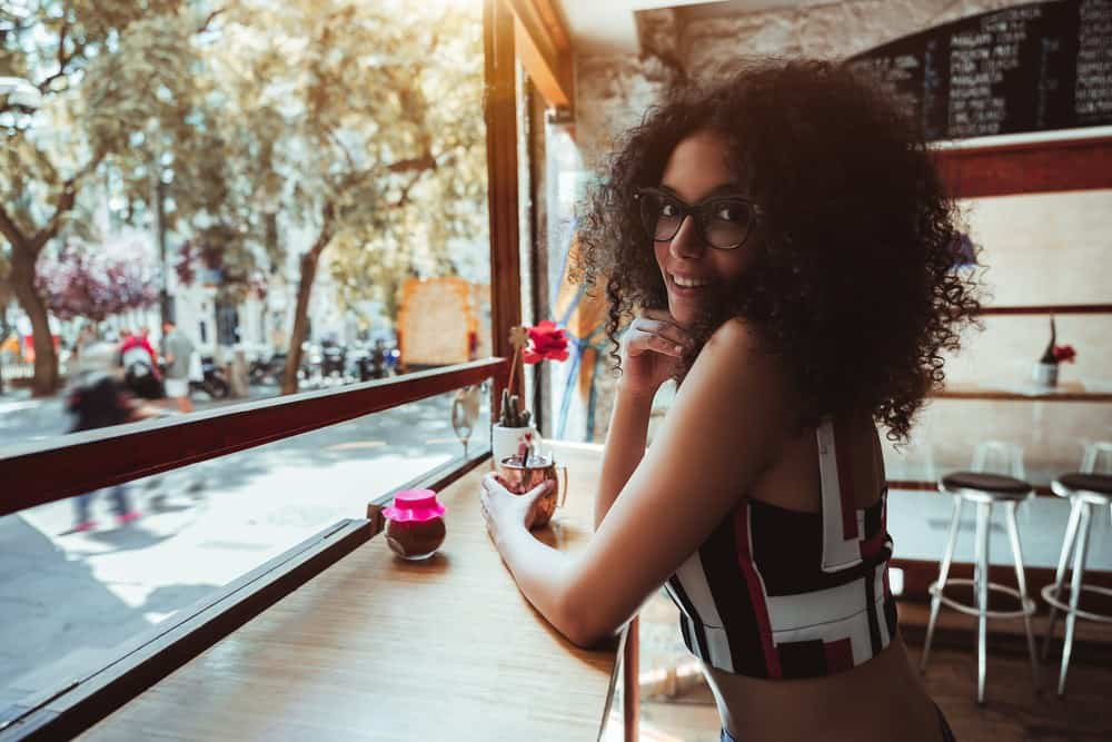 Cute Indian women wearing eye glasses with hair treated by arnica oil sitting at a bar drinking coffee.