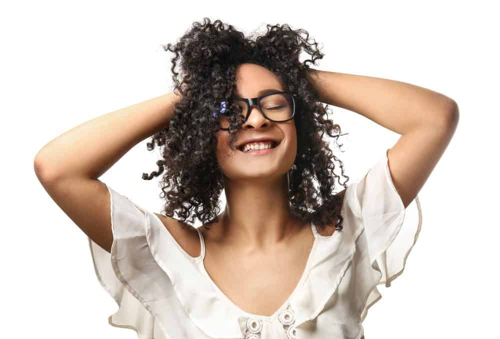 African American women smiling after using baobab oil on her hair for growth. She's wearing a white shirt with black glasses and naturally curly hair.