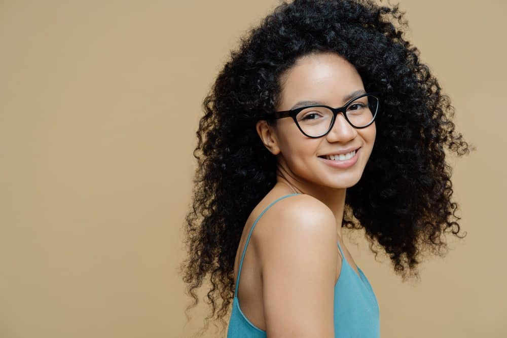 African American woman with naturally curly hair ready to learn how to use bergamot essential oil for her hair growth needs.