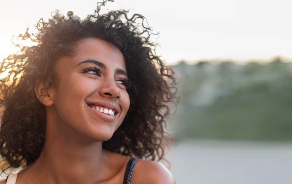 Outdoor portrait of beautiful smiling African American woman wearing a sundress.