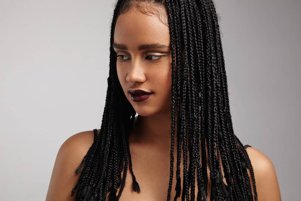 African American woman looking to her right wearing long weave hair extensions.