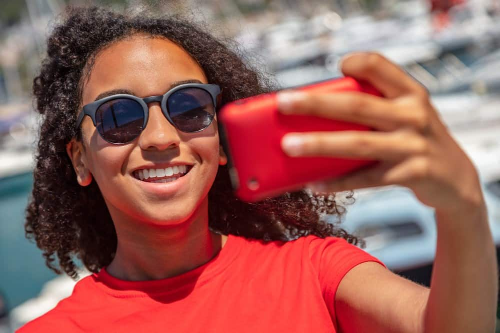 Beautiful African American woman  wearing sunglasses, a red t-shirt, and smiling with perfect teeth taking selfie photograph with red i-phone in the summer sunshine by a luxury boat filled harbor. The woman has very curly black and brown hair that's been moisturized with coconut oil.