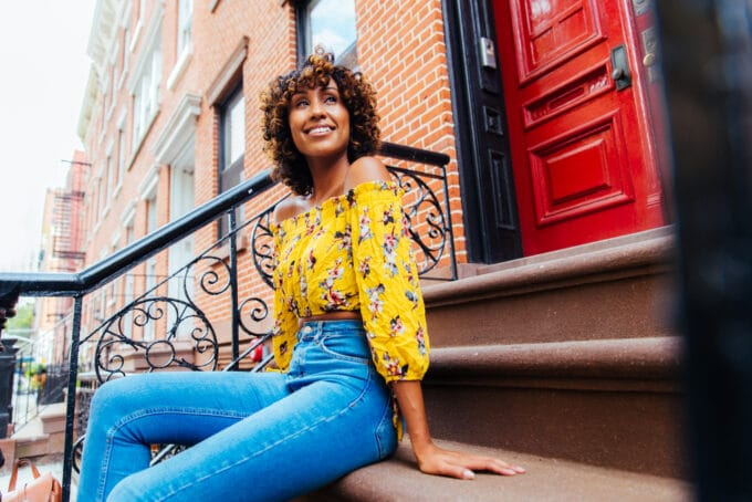 Black woman sitting outside an apartment building on stairs wearing a yellow shirt and blue jeans