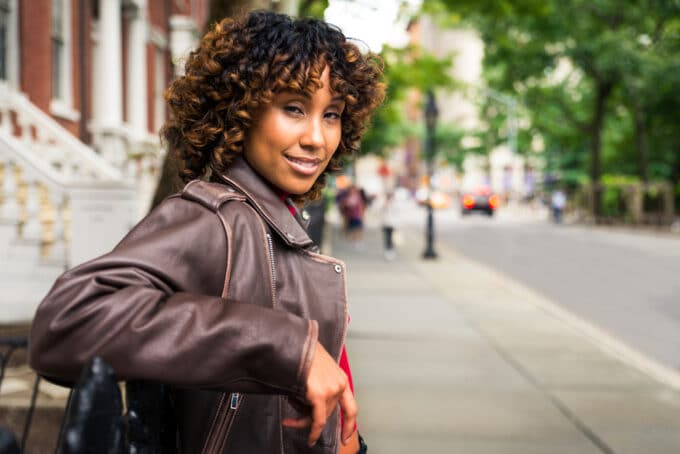 Close-up outdoor image of a black girl wearing a leather jacket with natural hair