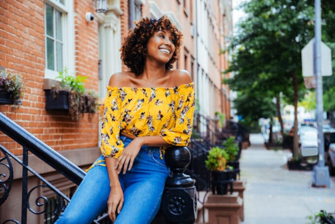 Lady leaning on a staircase railing looking into the distance with a huge smile