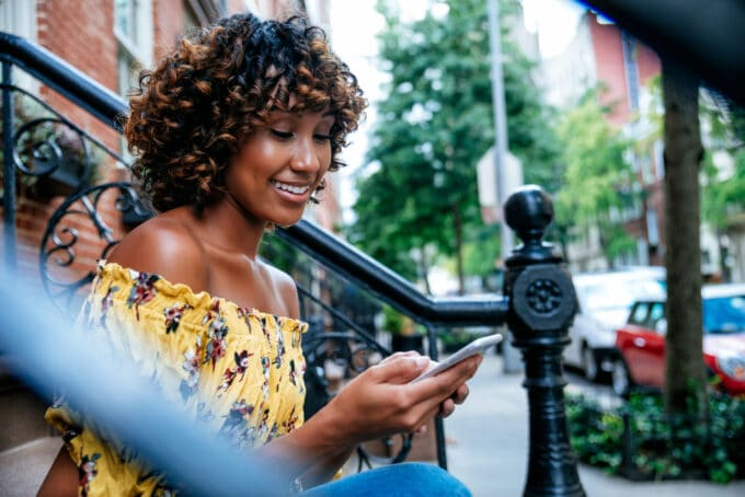 Black girl with 4b curls sitting onside while using her Apple iPhone
