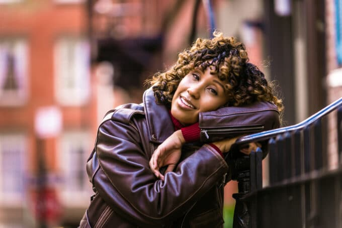 Black girl resting her head on a staircase railing wearing a leather jacket and ombre natural hair