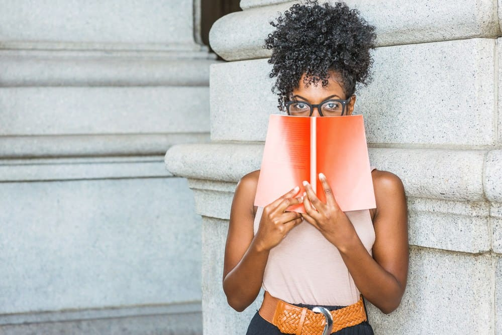 Pretty black girl wearing a pink shirt, brown belt while reading a book outside the library. She's wearing black glasses and has naturally curly type 4A hair.