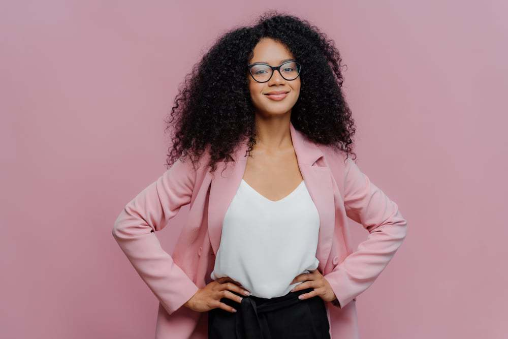 Mixed raced business woman wearing a pink blazer, white t-shirt and black glasses with black curly hair.
