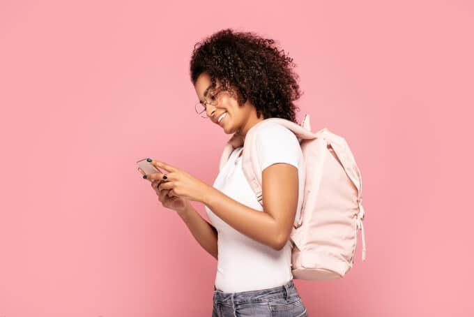 African American female with type 3 curly hair wearing a white t-shirt and a pink backpack.
