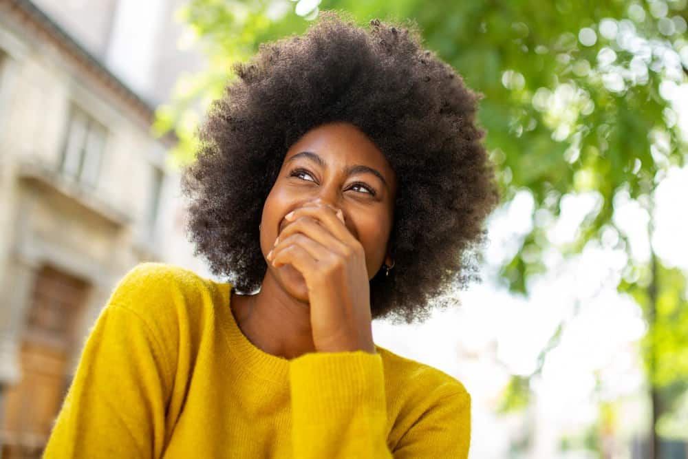 Black girl wearing a sweater with type 4D naturally curly hair.