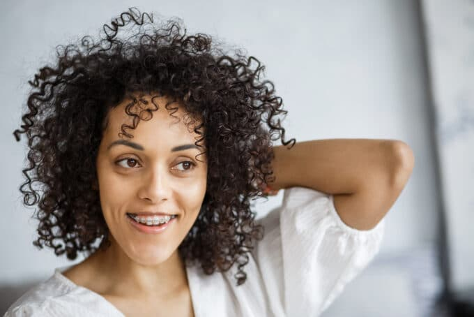 Black lady with braces rubbing her hands through her type 3c naturally curly hair strands.