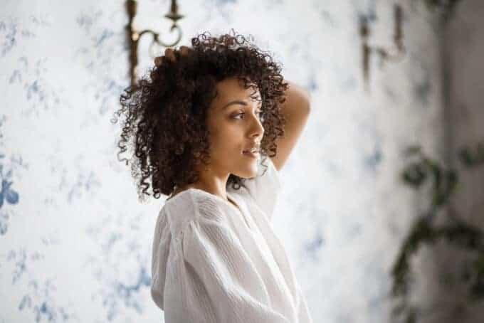 Black woman looking in the mirror rubbing her type 3c curly hair.