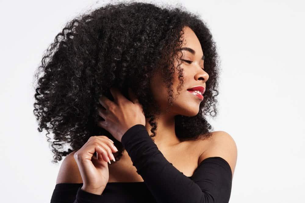 Black women rubbing her fingers through her 4c hair strands.