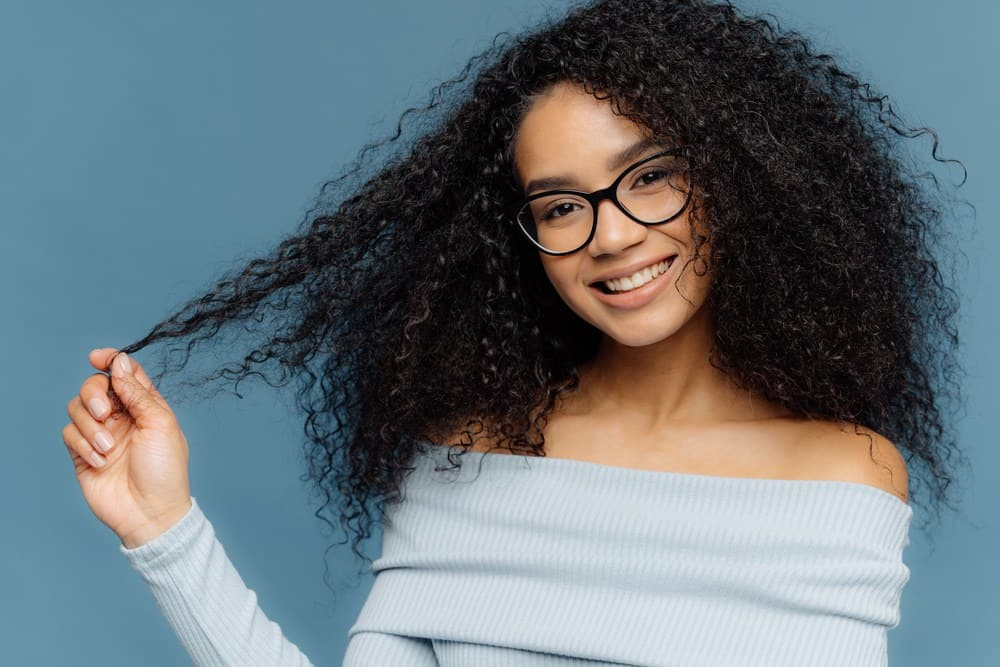 African American woman naturally curly type 3a hair that's been treated with bergamot oil for hair growth wearing a blue sweater and reading glasses.