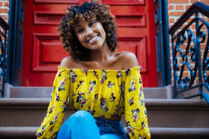 Light skin black girl sitting outside an apartment building on the stairs wearing a yellow shirt and blue jeans.