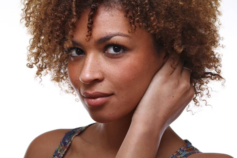 Beautiful African American female with naturally curly hair looking directly into the camera.