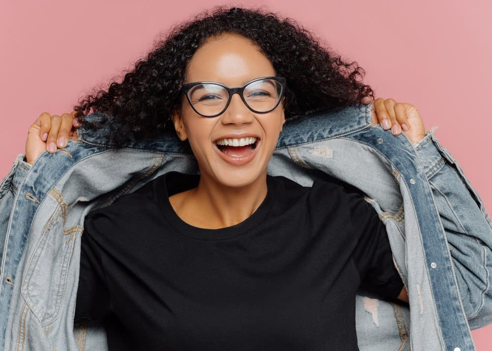 Back lady with a huge smile wearing a blue jean jacket and type 3B curly hair with a black undershirt.