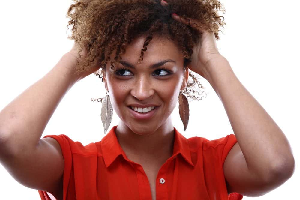 Pretty African American female wearing a red shirt with naturally curly hair.