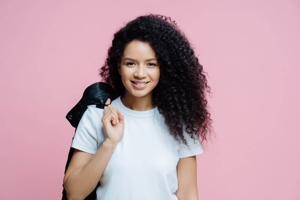 Ethnic African American woman with curly hair wearing a white t-shirt and carrying a black leather jacket over her shoulder.