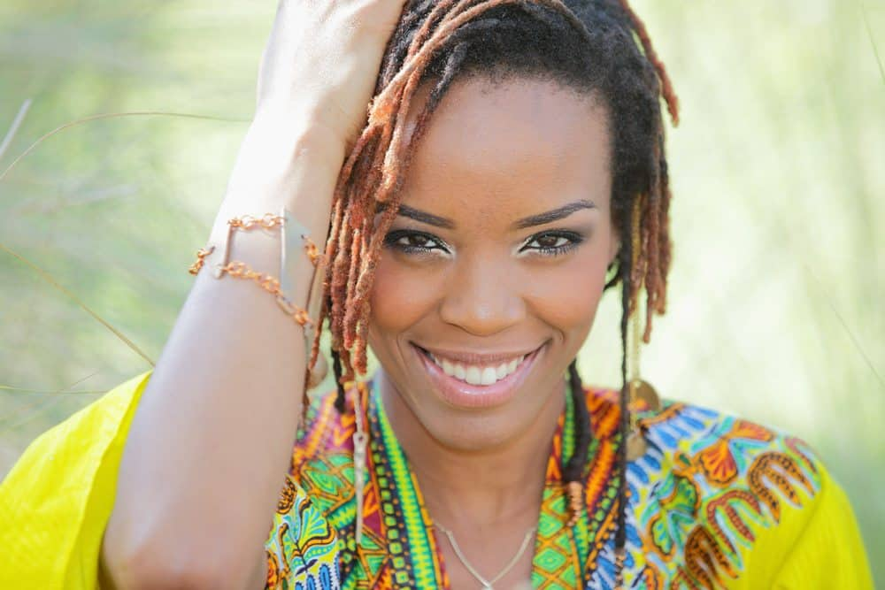 African female wearing a multi-colored shawl holding her 4C natural hair.