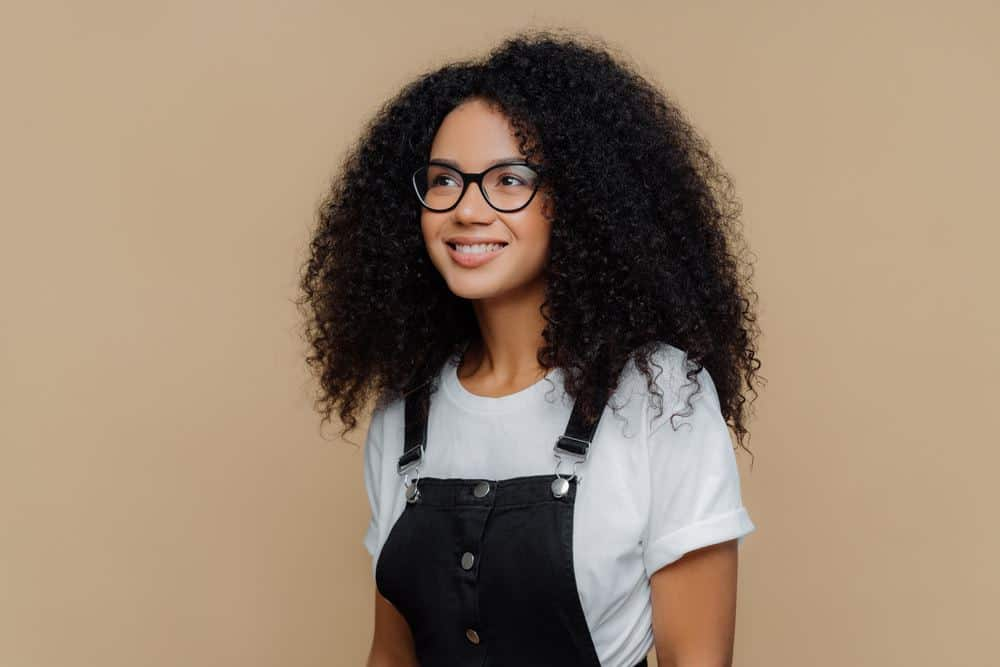 Cute American woman wearing black Tommy Hilfiger overalls and a white Hanes t-shirt with natural hair.