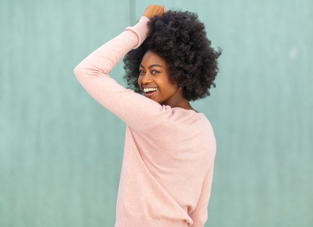 African American women with naturally curly hair looking back at the camera with a huge smile, wearing a oink sweater and earrings.