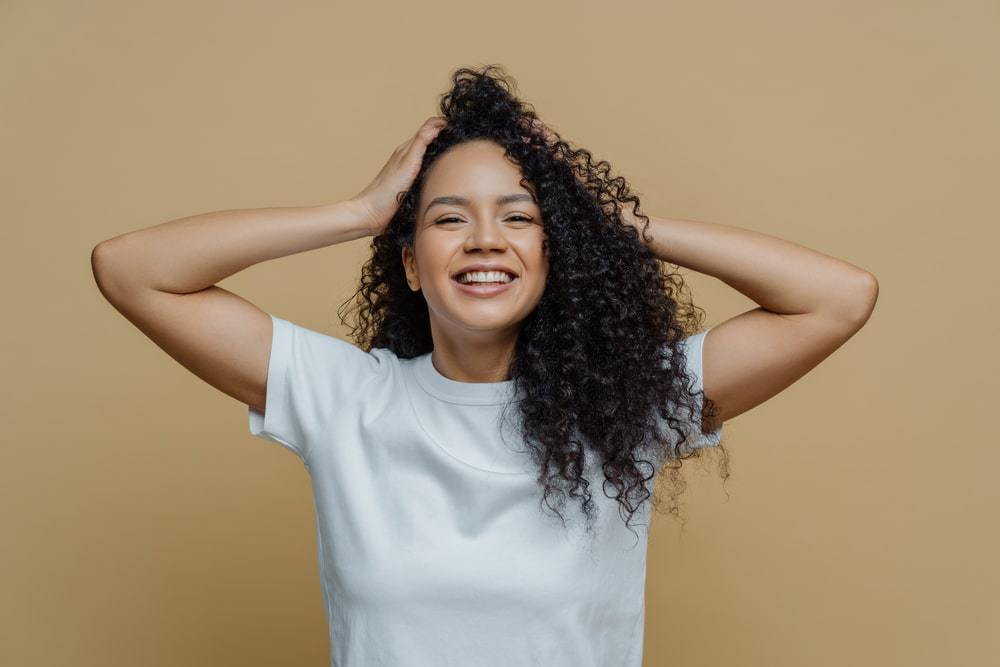 Happy black girl with curly hair holding her hair strands that were moisturized with bergamot oil while wearing a white t-shirt.